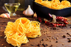 Raw spaghetti or pasta with sunflower oil, garlic, pepper and spice on black background, front view place for text Royalty Free Stock Photos