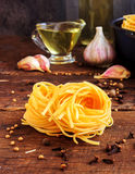 Raw spaghetti or pasta with sunflower oil, garlic, pepper and spice on black background, front view place for text Stock Photo