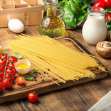 Raw spaghetti with set of ingredients for cooking Italian pasta Stock Image