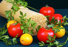Raw spaghetti tie a ribbon, tomatoes and parsley. Royalty Free Stock Images