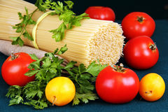 Raw spaghetti tie a ribbon, tomatoes and parsley. Stock Photography