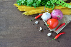 Raw spaghetti with tomato, garlic, onion and pepper, ingredients on brown wooden table. Royalty Free Stock Images