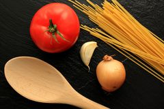 Raw spaghetti with tomato, garlic, onion and wooden trowel Royalty Free Stock Photos