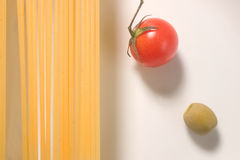 Raw spaghetti tomato and olive. Some raw spaghetti tomato and olive on a white background royalty free stock images