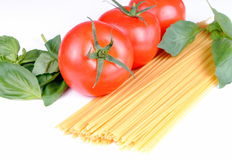 Raw spaghetti, tomatoes and basil on white Stock Photography
