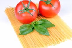 Raw spaghetti, tomatoes and basil on white Royalty Free Stock Image