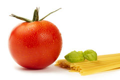 Raw spaghetti with wet tomato and basil. On white background Stock Photo