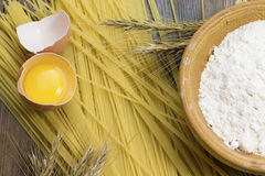 Raw spaghetti, wheat stalk, egg and flour. On wooden desk Royalty Free Stock Images