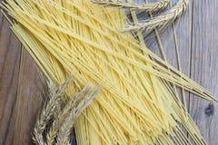 Raw spaghetti and wheat stalk. On wooden desk Stock Photos