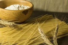 Raw spaghetti and wheat stalk. On wooden desk Royalty Free Stock Photography