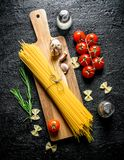 Raw spaghetti on a wooden cutting Board with garlic, tomatoes and rosemary royalty free stock photography