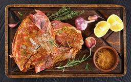 Raw spare lamb ribs with spices. Raw spare lamb ribs marinated to be cooked with rosemary, thyme, mix of spices, garlic and lemon slices on wooden rustic cutting Royalty Free Stock Image