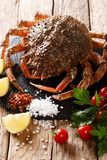 Raw spider crab for cooking with spices, vegetables ingredients. Close-up on the table. Vertical stock image