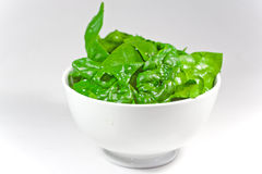 Raw spinach leaves. In a white bowl with white background Stock Photos