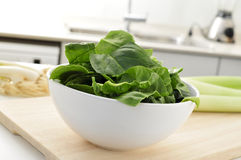 Raw spinach leaves on the countertop of a kitchen. A bowl with spinach leaves on a wooden chopping board on the countertop of a kitchen Stock Photo