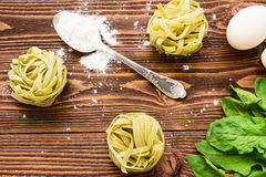 Raw spinach pasta on wooden background Royalty Free Stock Images