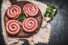 Raw spiral sausages on wooden cutting board, top view. Place for text Stock Photo
