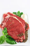 Raw steak. Fresh steak closeup, with basil, garlic, pepper, parsley Stock Image