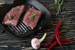 Raw steak on cast iron frying pan with garlic and pepper. Stock Images
