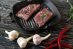 Raw steak on cast iron frying pan with garlic and pepper. Stock Photo