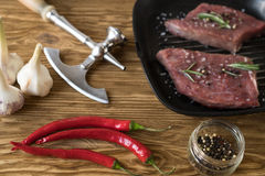 Raw steak on cast iron frying pan with garlic and pepper. Royalty Free Stock Images