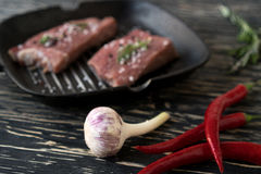 Raw steak on cast iron frying pan with garlic and pepper. Royalty Free Stock Photo