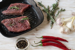 Raw steak on cast iron frying pan with garlic and pepper. Stock Photography