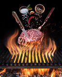 Raw Steak cooking. Conceptual picture. Steak with spices and cutlery under burning grill grate royalty free stock photos