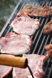 Raw steak cooking on grill Stock Photos