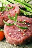 Raw Steak with green asparagus Stock Photos