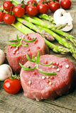 Raw Steak with green asparagus on wooden board Royalty Free Stock Image