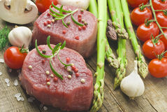 Raw Steak with green asparagus on wooden board Stock Photos