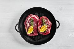 Raw Steak in grill frying pan with herbs and oil on white background, top view, place for text stock photos