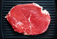 Raw steak in iron grilled pan. Close up Royalty Free Stock Photos