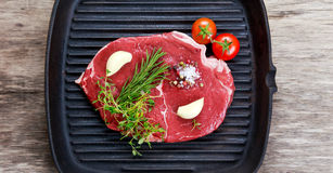 Raw steak in iron grilled pan with herb. Raw steak in iron grilled pan with herb Stock Images