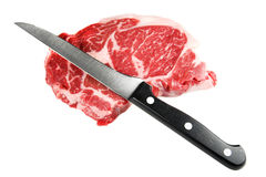 Raw steak and Knife. Whole raw beef steak and knife isolated against white Royalty Free Stock Photo