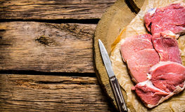Raw steak with a knife on a wooden stand. On a wooden table. Free space for text . Top view Royalty Free Stock Photos