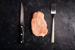 Fresh raw meat on wooden board. Raw steak meat on black wooden table next to fork and knife. Gourmet food and fresh uncooked meal Stock Image