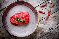 Raw steak in the pan with garlic and pepprs Royalty Free Stock Photo
