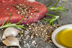 Raw Steak with Peppercorns Rosemary Garlic and Olive Oil. Raw beef steak with peppercorns, rosemary, garlic cloves and olive oil Royalty Free Stock Image