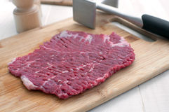 Raw steak piece and meat pounder Royalty Free Stock Image
