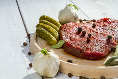 Raw steak ready to grill. On old wooden plank Stock Image