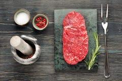 Raw steak Ribeye entrecote on dark wooden background Royalty Free Stock Photo