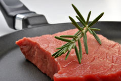 Raw  steak with rosemary in a pan Royalty Free Stock Photos