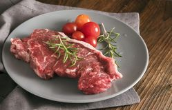 Raw steak with rosemary and tomatoes on a gray plate on rustic w Royalty Free Stock Images