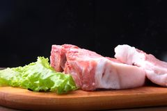 Raw steak on a rustic cutting board with salt, pepper and grinder for spices . Black Background for copy space. Top View. Raw steak on a rustic cutting board Stock Image