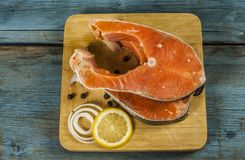 Fresh raw salmon steaks with salt, peppers, lemon. Raw steak of salmon with fresh lemon and pepper peas on the wooden board Royalty Free Stock Photography