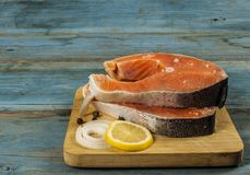 Fresh raw salmon steaks with salt, peppers, lemon. Raw steak of salmon with fresh lemon and pepper peas on the wooden board Stock Photography