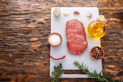 Raw Steak with spices. View from above is a place for a test. Steak with spices top view. Marble meat from veal, there are pepper, salt, garlic and olive oil royalty free stock images