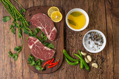 Raw steak with spices on wooden background. Royalty Free Stock Photography